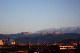 雪を纏った山が朝陽色に染まる